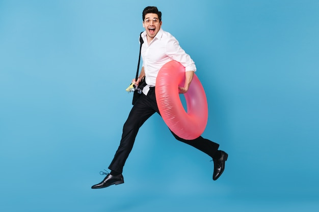 Man in white shirt and black trousers runs against blue space, happily smiles and holds inflatable circle.