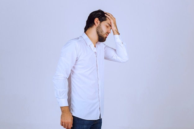 Man in white shirt coverin his face, feels sad and has headache.