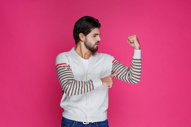 Uomo in camicia bianca che dimostra i suoi muscoli del braccio e la potenza.