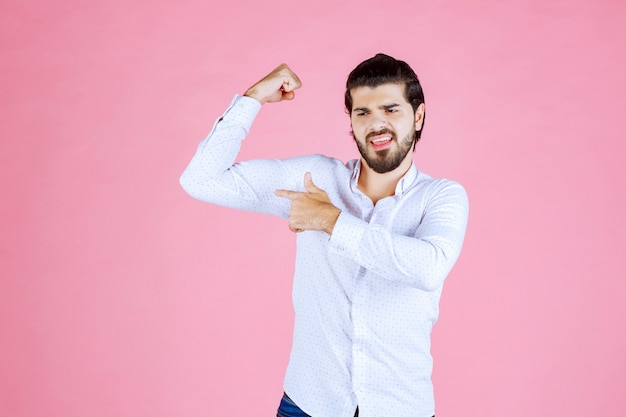 Man in a white shirt demonstrating his arm muscles.