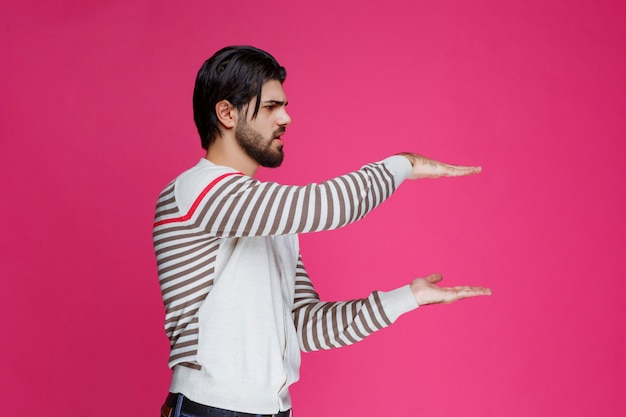 Uomo in camicia bianca che dimostra le misure di un pacco.