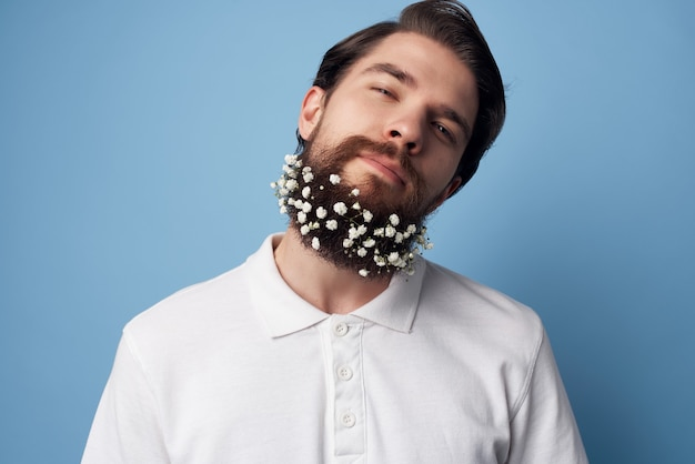 Man in white shirt emotions beard with flowers decoration blue background