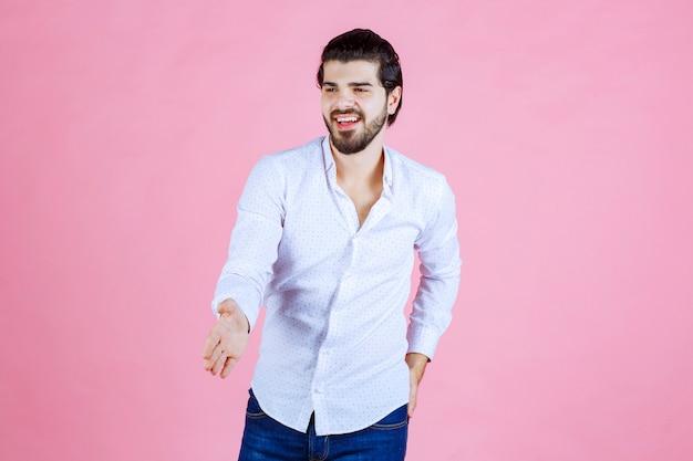 Uomo in una camicia bianca che dà la mano per scuotere.