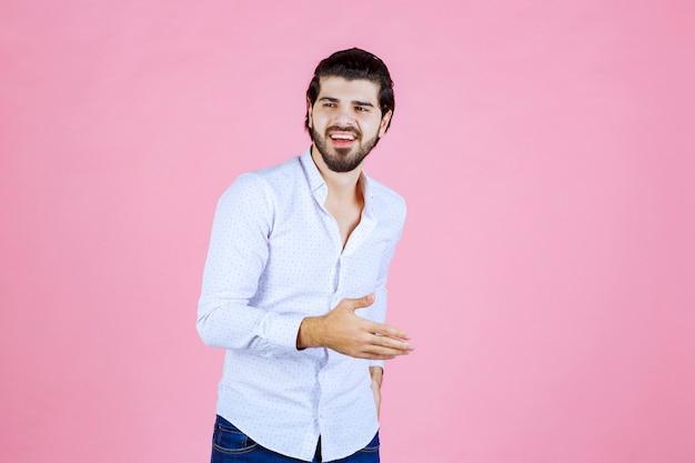 Uomo in una camicia bianca che dà pose neutre e accattivanti.