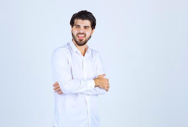 Uomo in camicia bianca che fa pose neutre