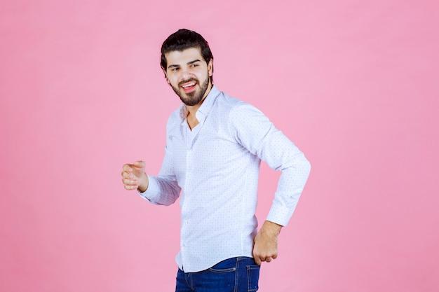 Uomo in una camicia bianca che dà pose sorridenti e positive.