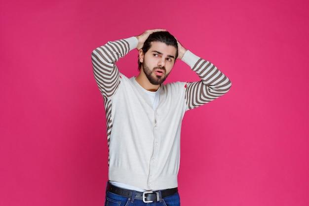Man in white shirt has headache and holding his head.