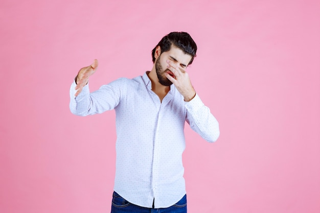 Man in a white shirt holding breath as he feels bad smell.