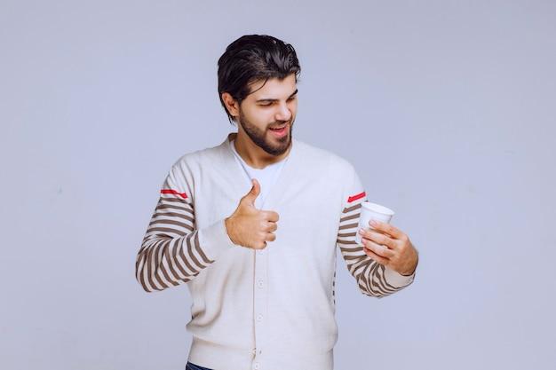 Uomo in una camicia bianca che tiene una tazza di caffè.
