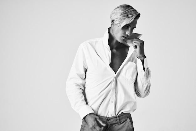Man in white shirt holding collar elegant style selfconfidence studio