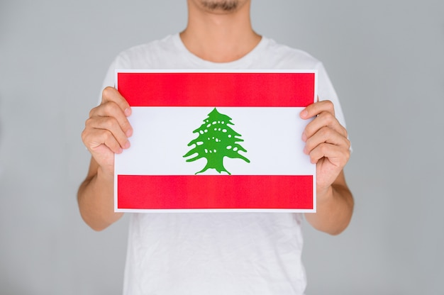 Man in a white shirt holding the flag of lebanon.