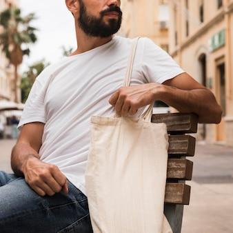 Man in white shirt holding shopping bag