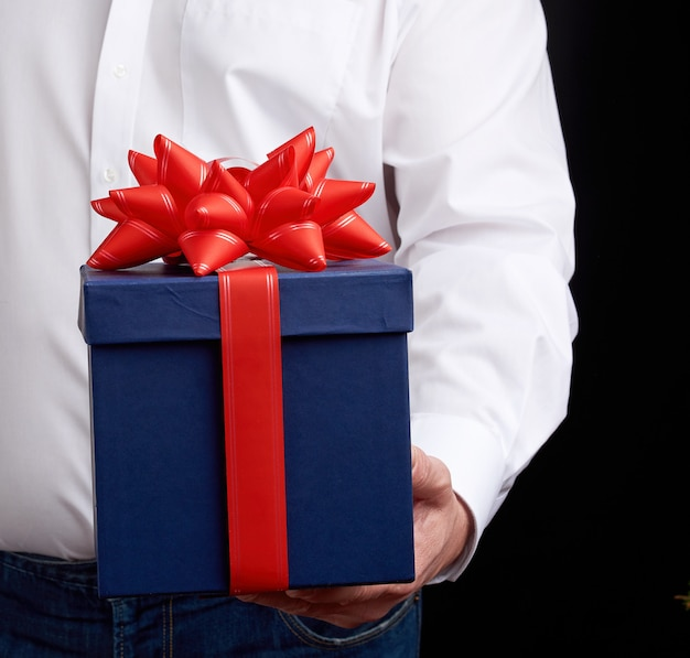Man in a white shirt holds a blue gift box with a red bow