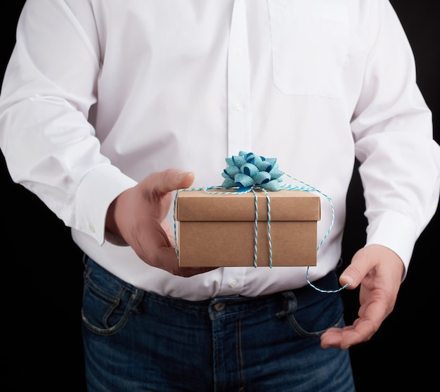 Man in a white shirt holds in his hand a closed brown gift box on a dark background
