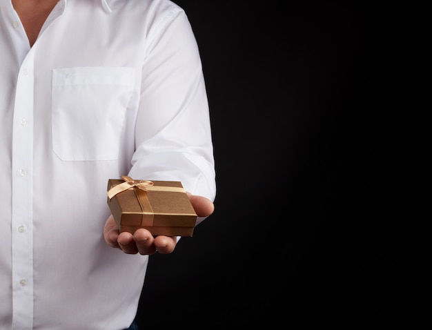 Man in a white shirt holds in his left hand a little golden box