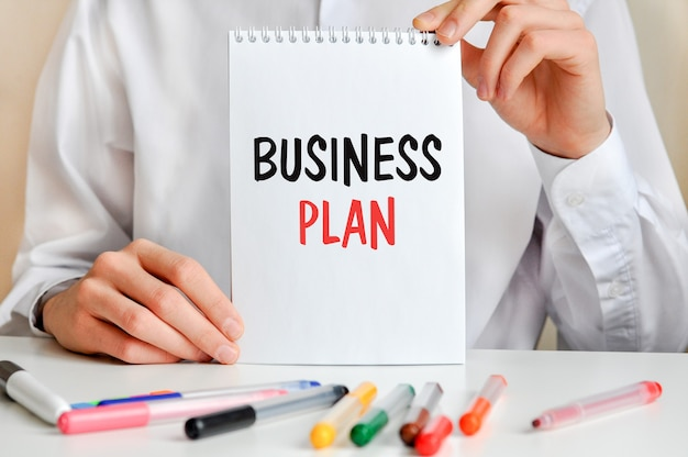 A man in a white shirt holds a piece of paper with the text: business plan. multicolored markers and tablet on a table. business and educational concept for companies and educational institutions.