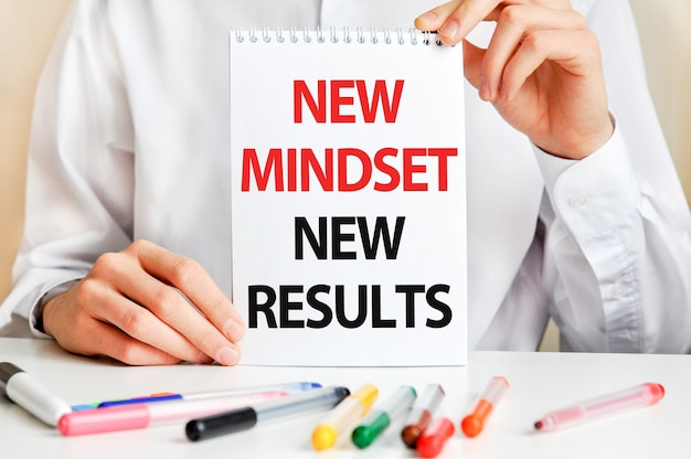 A man in a white shirt holds a piece of paper with the text: new mindset new results. multicolored markers and tablet on a table. business and educational concept.