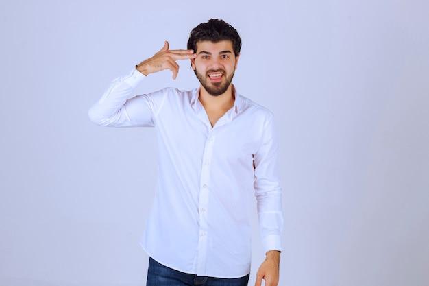 Uomo in camicia bianca che guarda e pensa.