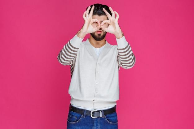 Uomo in camicia bianca, guardando attraverso le dita.