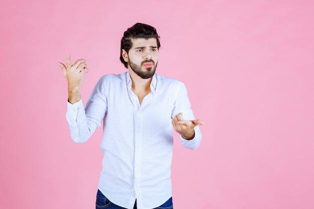 L'uomo con una camicia bianca sembra confuso e cerca di spiegarsi mentre usa i gesti delle mani.