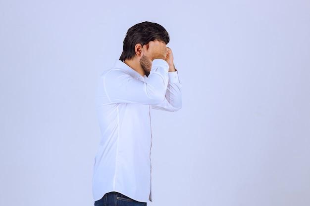 Man in white shirt looks sleepy or sad.