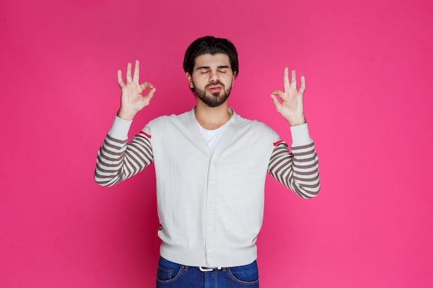 Uomo in una camicia bianca che fa il segno della mano di meditazione o di piena soddisfazione.