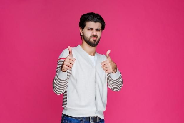 Uomo in una camicia bianca che fa il pollice sul segno.