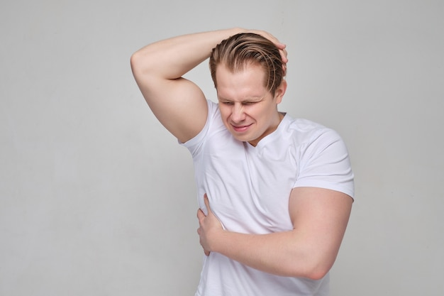 A man in a white shirt massages the area of the ribs. the concept of pain and neurology.
