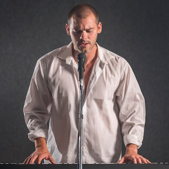 Man in white shirt playing keyboards and sings