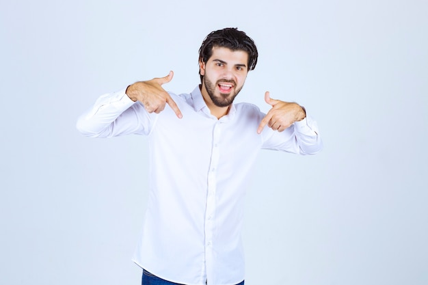 Uomo in una camicia bianca che indica se stesso.