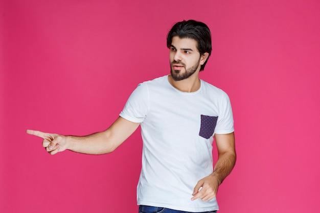 Uomo in camicia bianca che punta a qualcosa a sinistra.