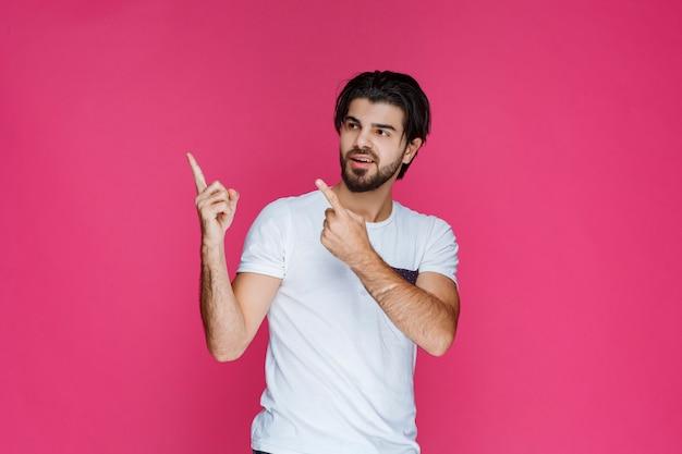 Uomo in camicia bianca che punta a qualcosa di cui sopra.