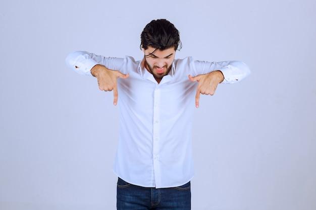 Uomo in camicia bianca che indica qualcosa di seguito.