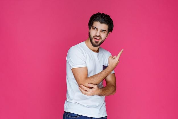 Uomo in camicia bianca che indica da qualche parte e presenta qualcuno o mostra semplicemente la direzione.