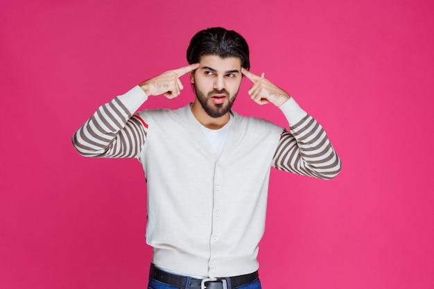 Man in white shirt putting hand to his head like he is thinking deep and trying to remember