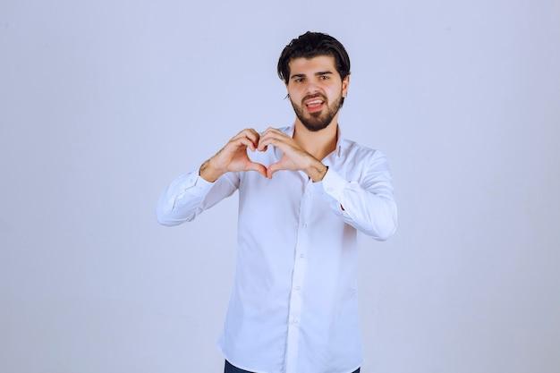 Uomo in camicia bianca che invia amore e cuore.