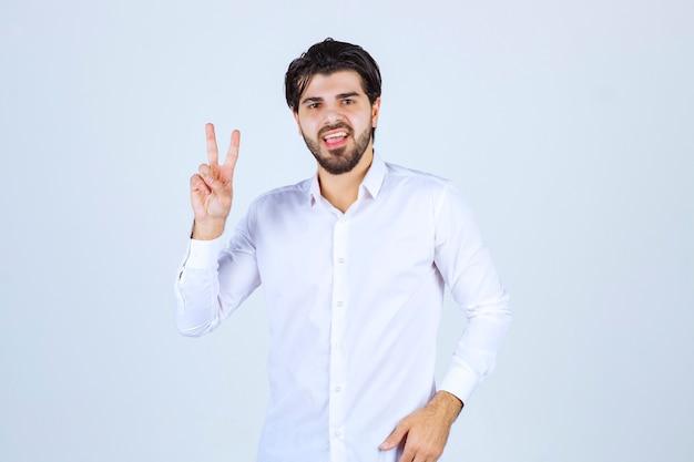 Uomo in camicia bianca che invia un messaggio di pace e amicizia