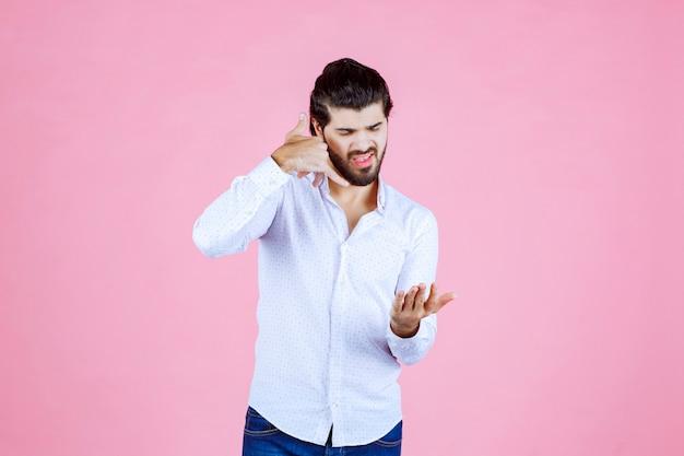 Uomo in una camicia bianca che mostra il segnale di chiamata.