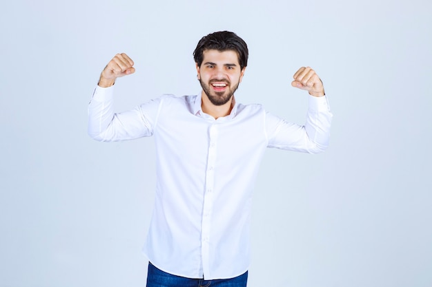 Man in white shirt showing his arm muscles and fist.