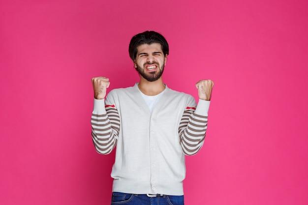 Uomo in camicia bianca che mostra i suoi pugni e il potere.
