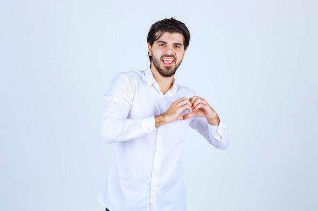 Uomo in camicia bianca che mostra il suo cuore e invia amore