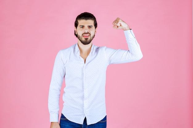 Uomo in camicia bianca che mostra i suoi potenti pugni.