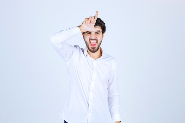 Man in white shirt showing loser sign.
