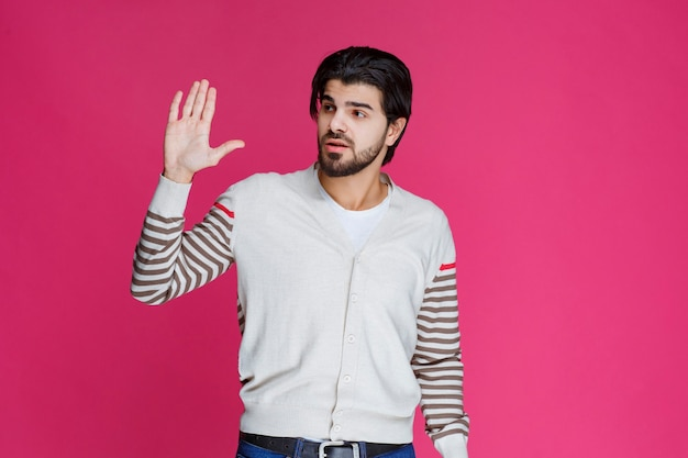 Uomo in una camicia bianca che mostra qualcosa in mano.
