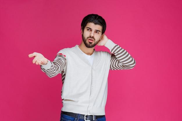 Uomo in camicia bianca che mostra di non avere idea dell'argomento.