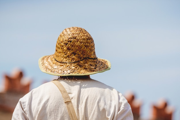 Man in white shirt and straw hat on blue sky background in sunny weather