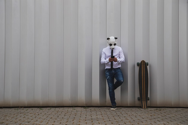Man in white shirt, tie and panda bear mask chatting with a smartphone. space for text