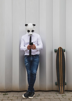 Man in white shirt, tie and panda bear mask chatting with a smartphone