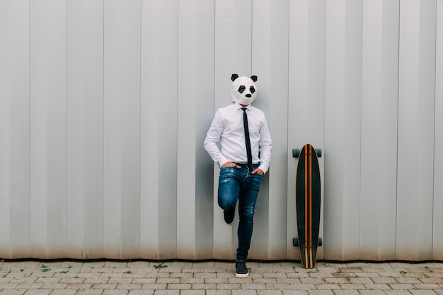 Man in white shirt, tie and panda mask leaning against a gray wall with a longboard