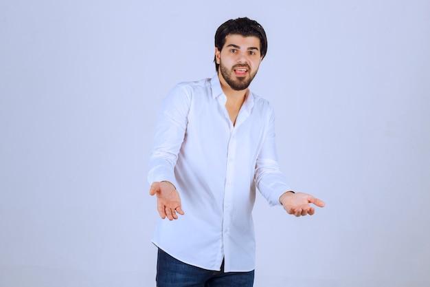 Uomo in camicia bianca che cerca di spiegare se stesso.